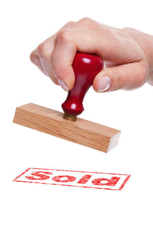 Hand holding a rubber stamp with the word Sold photo