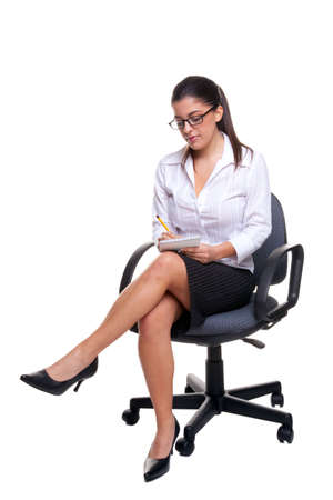 legs crossed: Attractive young secretary sat on an office chair taking notes, isolated on a white background.