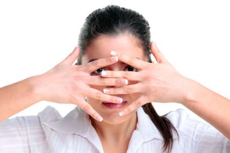 peek a boo: Brunette woman looking through her fingers, isolated on a white background.