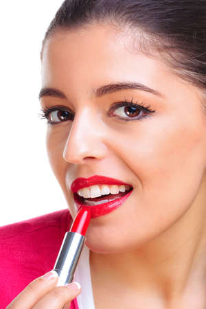 A brunette woman applying red lipstick photo