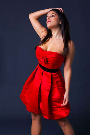 Woman with long dark hair in a red cocktail dress photo