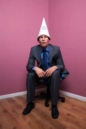 sat: A businessman sat in the corner of the room wearing a dunces hat with a dumb expression on his face.