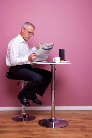 stool: Businessman sat in a cafe reading the morning news, the newspaper has had any copyright issues removed and the text is unreadable. The menu is blank also.