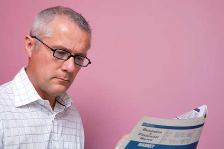 share prices: Businessman reading the latest share prices in a financial newspaper