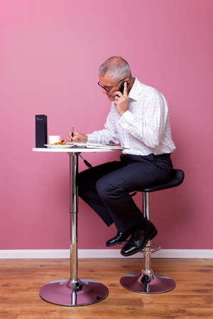Businessman in smart casual attire sat on a bar stool in a cafe working through his lunch break. photo