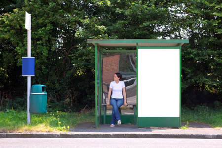 A woman sat in a rural bus shelter next to a blank advertising billboard photo