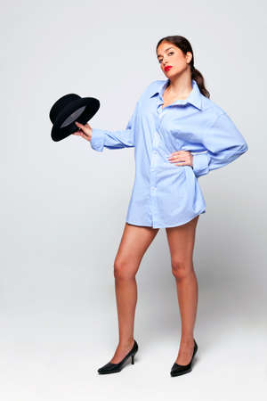 A brunette woman with long legs wearing a mans shirt and holding a bowler hat Stock Photo - 5663011