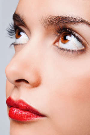 Close up face portrait of a woman with big brown eyes and bright red lips photo