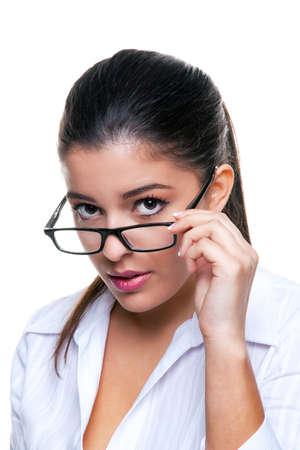 Attractive businesswoman regarde par-dessus ses lunettes, fond blanc.
