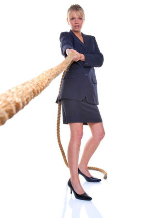 Blonde businesswoman pulling on a piece of rope, focus on her. Isolated on a white background. photo