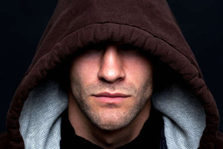 hooded: An evil looking man wearing a hooded top with his eyes hidden against a black background. Stock Photo