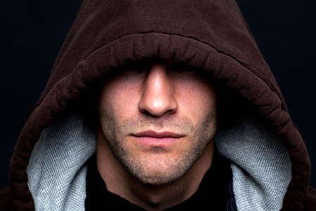 rapinatore: Un male che cercano l'uomo indossava un top incappucciato con gli occhi nascosti su uno sfondo nero. Archivio Fotografico