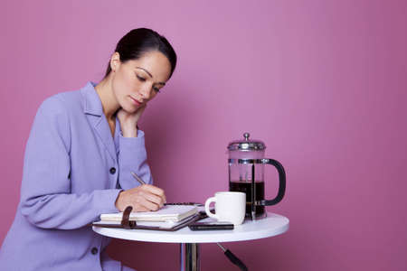 Businesswoman writing in her diary during a coffee break Stock Photo - 5840865