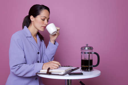 Businesswoman sat at a table in a cafe drinking coffee photo