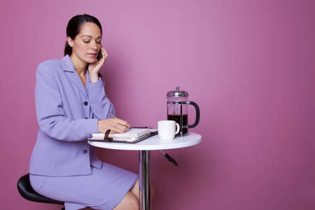 Businesswoman sat at a table in a cafe talking on her mobile phone during a coffee break photo