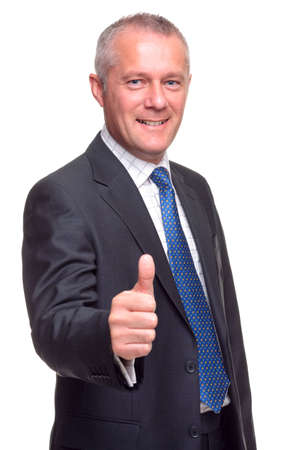 Mature businessman in suit and tie giving a thumbs up gesture towards camera, isolated on a white background. photo