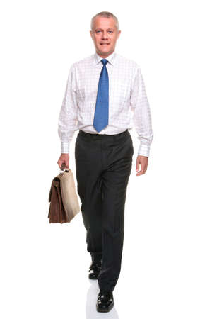 attache: Mature businessman in shirt and tie walking towards carrying a briefcase, isolated on a white background.