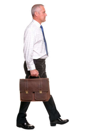 people walking white background: Mature businessman in shirt and tie walking towards carrying a briefcase, Ive left shadow under the feet where grounded and there is a small amount of motion blur on his legs.