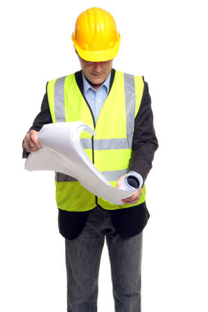 Building contractor wearing safety clothing as he unfolds some blueprints, isolated on a white background. photo