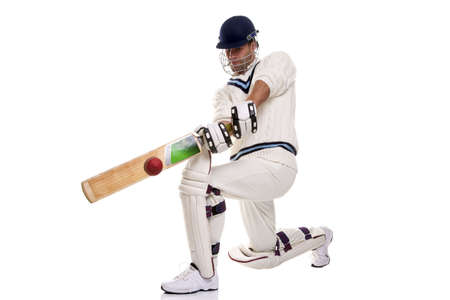 Cricketer down on his knee playing a shot, studio shot on white background. photo