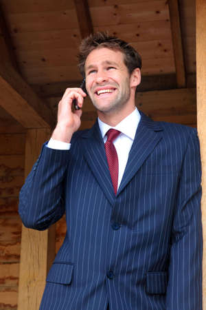 Businessman in his late twenties standing at a rural bus stop talking on his mobile phone Stock Photo - 5955294