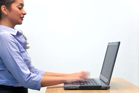 emphasise: A woman typing on a laptop computer with motion blur on her fingers to emphasise speed. Stock Photo