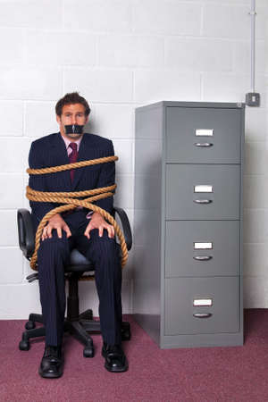 hostage: Businessman tied to an office chair with rope, look of fear on his face. Stock Photo