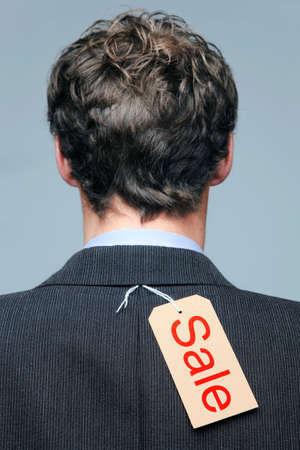 Rear view of a male wearing a suit jacket with a Sale label on it. photo
