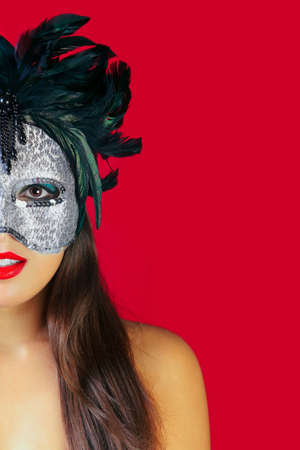 dressing up costume: Beautiful brunette woman wearing a masqurade mask against a red background.