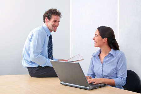 Two business people enjoying a light hearted moment in the office. Stock Photo - 5840868