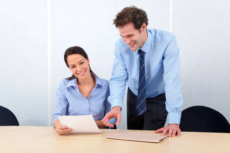 Two business people in an office the woman smiling at camera. Stock Photo - 5840853