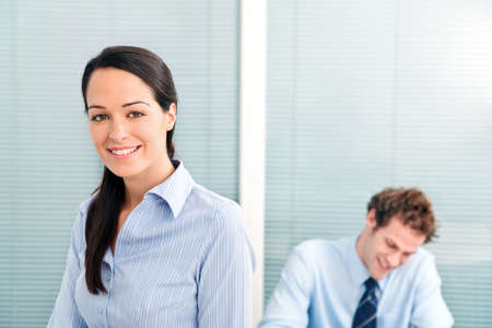 Businesswoman in an office smiling to camera, male colleague in the background out of focus. Stock Photo - 5840855