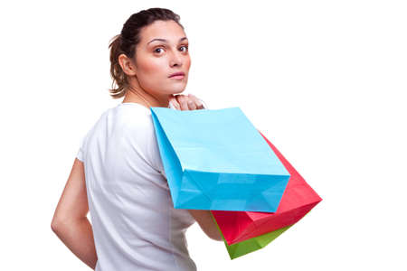 A young attractive brunette woman carrying some colorful shopping bags as she looks back over her shoulder, isolated on a white background. Blank bags for your own message. photo