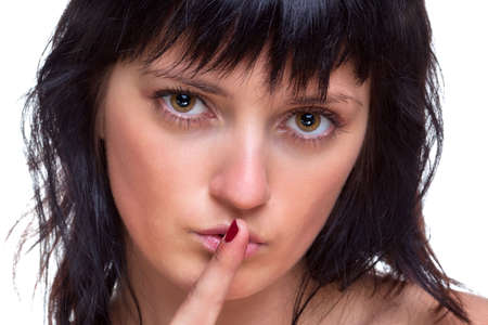 Brunette woman telling you to be quiet, finger on lips, white background. photo