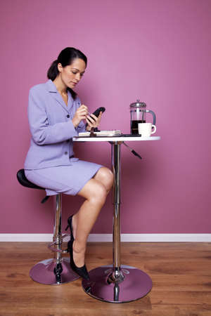 Businesswoman sat at a cafe table writing on her mobile phone during a working lunch. Stock Photo - 5955336