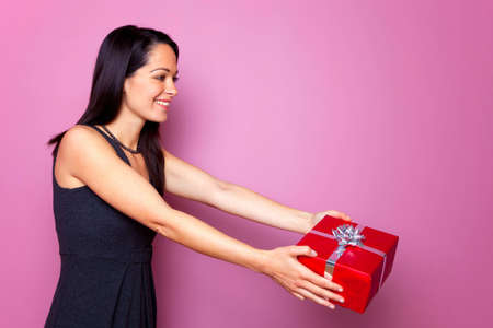 A brunette woman wearing a black dress handing over a gift. photo