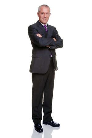 man looking out: Full length shot of a mature businessman wearing a suit with his arms folded looking at camera.