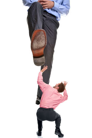 A businessman about to be stepped on by a giant foot, isolated on a white background.