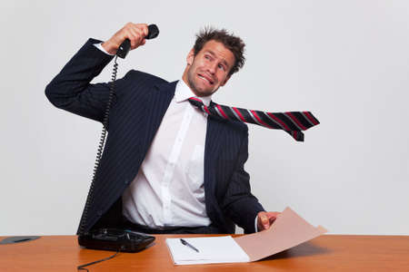 irate: Businessman getting a phone call from an angry person shouting down the line.