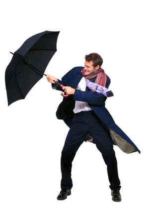 Studio Shot der ein Geschäftsmann mit einen Regenschirm in den Wind, auf einem weißen Hintergrund isoliert.