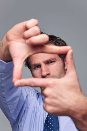 perspective: Businessman making a frame with his hands, focus on his face hands blurred.