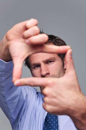Geschäftsmann machen einen Frame mit seinen Händen, Fokus auf seine Gesicht, Hände verschwommen.
