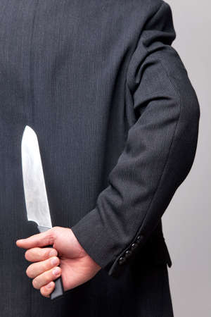 con man: Close up of a businessman with a knife behind his back.