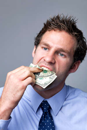 A businessman stuffing bank notes in his mouth. photo