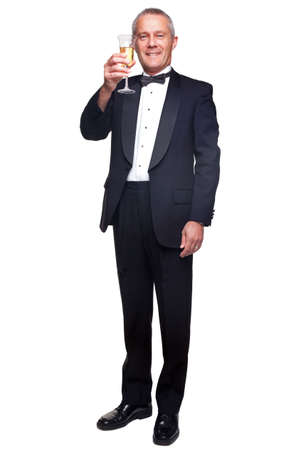 dinner wear: A mature male wearing a black tuxedo and bow tie raising a glass of champagne, isolated on a white background.