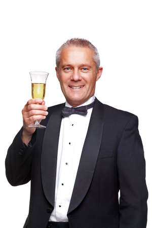 formal attire: A mature male wearing a black tuxedo and bow tie raising a glass of champagne, isolated on a white background.