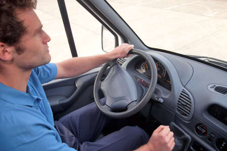 hand truck: Van driver in a left hand drive vehicle.  Also available as RHD, instrument panel is correct for both images. Stock Photo