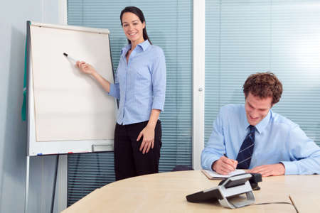 Businesswoman standing at a flip chart giving a presentation, male colleague sat at a table writing. Flip chart is blank to add your own text. photo