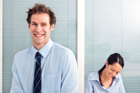 Businessman in an office smiling to camera, female colleague in the background out of focus. Stock Photo - 5955325