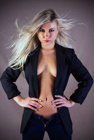 A beautiful blonde haired woman hands on hips with hair blowing, motion blur on her hair. There is some slight color noise on the background caused by the material. Stock Photo - 5978768